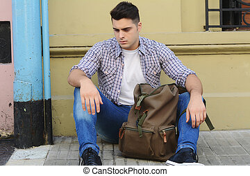 Young latin man sitting at the street