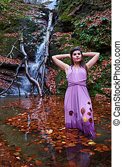 Young latin woman by a waterfall