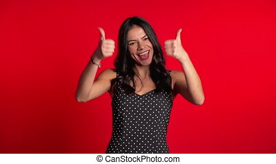 Young latin woman in dress with perfect make-up making thumbs up sign over red background. Winner. Success. Positive girl smiles to camera. Body language.