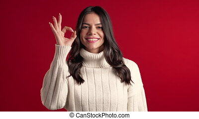 Young latin woman with perfect make-up in sweater making OK sign over red background. Winner. Success. Positive girl smiles to camera. Body language.