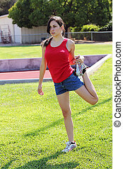 young latina teen girl stretching on green grass