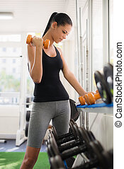 Young latina woman taking weights from rack in fitness club