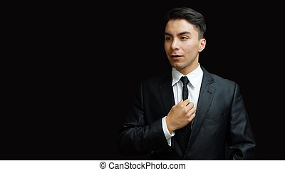 Young latino man in black suit, white shirt, black tie with...