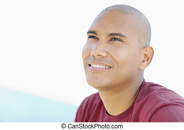 young latino man smiling and looking up