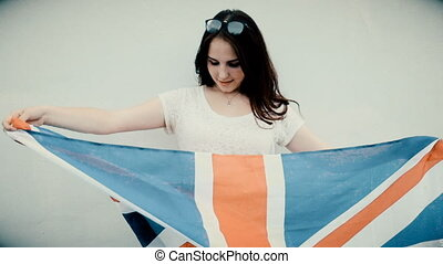 Young latino woman holds Union Jack flag in front of her...