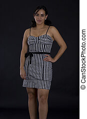 Young latino women in black in white dress with checkers motive
