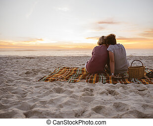 Young lesbian couple sitting on beach blanket watching the sunset