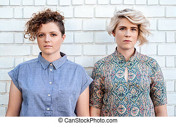 Young lesbian couple standing in front of a brick wall