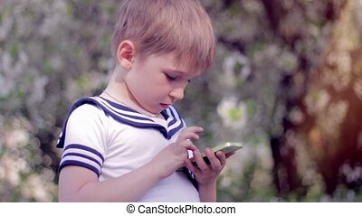 Young little boy plays games on smartphone. Spring park