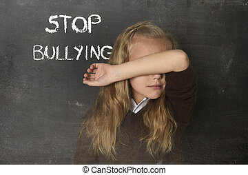 young little cute schoolgirl scared sad covering her face and the words stop bullying text
