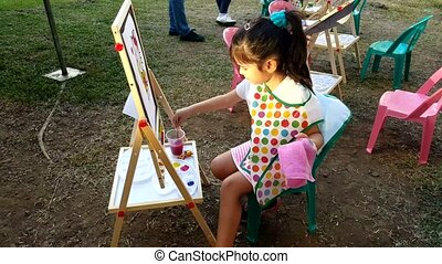 Young little girl artist painting outdoors