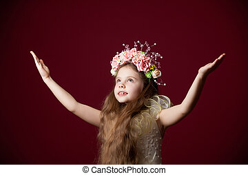 Young little girl in dress with wreath on red background