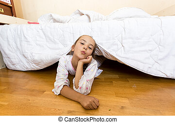 young little girl lying on floor at bedroom under bed
