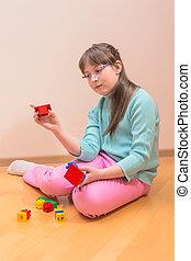 Young little girl sitting on floor