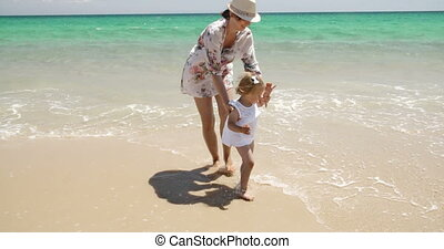 Young Little Girl With Her Mum on The Beach