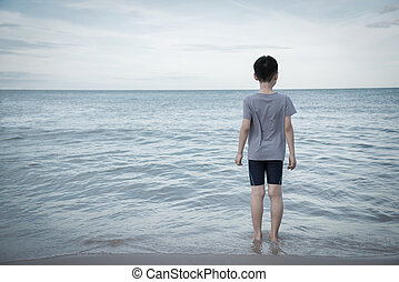 lonely boy looking to the ocean