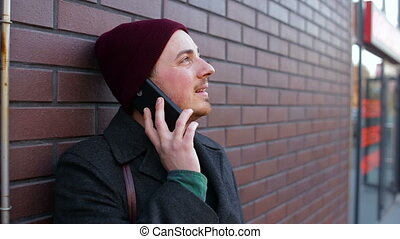 Young lonely man talking on the phone near the brick wall in the city