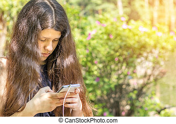 Young long haired girl using the phone in the city park on a...