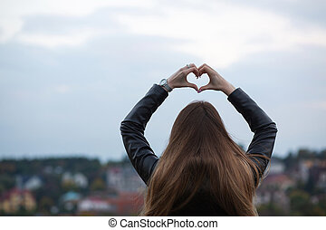Young long haired model showing heart symbol with two hands over a city background. Space for text