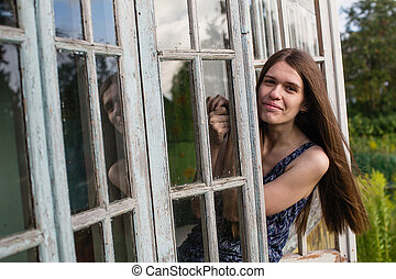 Young long-haired woman looks from of the window of the veranda.