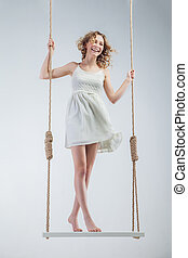 Young loughing bare-footed girl on swing looking in the ...