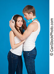 young love couple. Boy putting on headphones, listening music in the studio over blue background