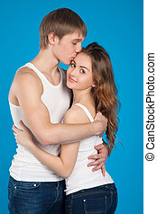 young love couple holding and kissing each other in the studio over blue background