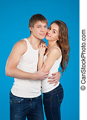 young love couple holding each other in the studio over blue background