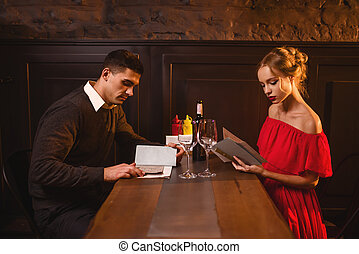 Young love couple look at the menu in restaurant
