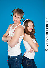 young love couple wearing headphones, listening music in the studio over blue background