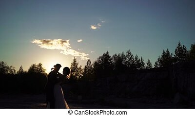 Young lovely couple hugging silhouette slowmotion