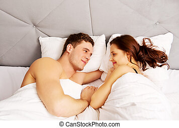 Young lovely couple in bed.