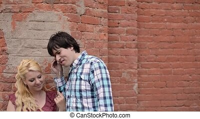 Young lovely couple listening music with earphones outdoors