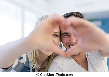 couple making heart with hands - Young lovely couple making...
