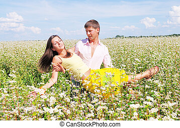 Young lovely couple playing on a flower field
