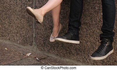 Young lovely couple sitting on embankment legs