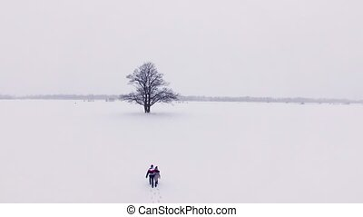 Young lovely couple walking in a winter snowly field