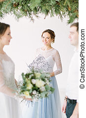 Young lovely couple with speech master of wedding ceremony against decor arch on wedding ceremony