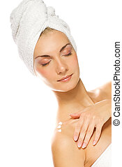 Young lovely lady applying moisturizer to her skin after shower