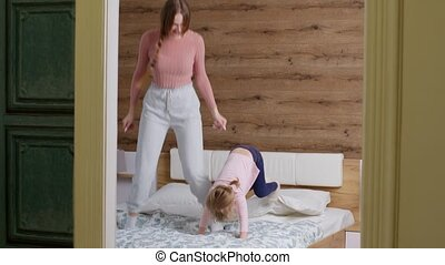 Young lovely mother babysiter and little kid daughter jumping dancing on bed in modern house bedroom