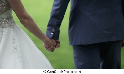 Young lovely wedding couple walking in park