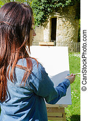 young lovely woman painting outdoors