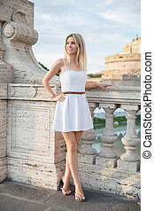 Young lovely woman posing on a bridge