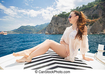 Young lovely woman posing on a yacht