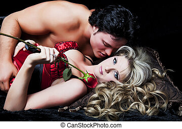 Young Lovers - Romantic couple in lingerie with red rose on...