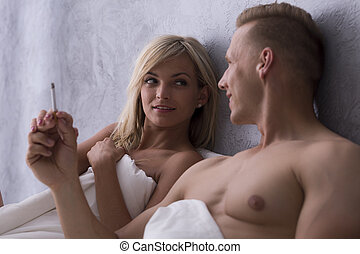 Young lovers smoking in bed