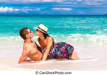young loving couple having fun in the tropical beach