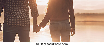Young loving couple holding hands at sunset