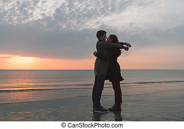 young loving couple hugging on the seashore in autumn