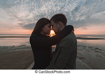young loving couple hugging on the seashore sunset in autumn